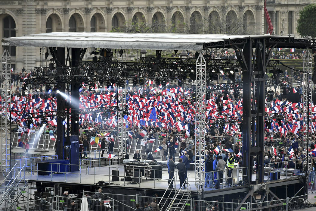 Supporters of incoming French President Emmanuel Macron wave French flags as the preliminary results of the runoff presidential election are announced at the Louvre museum in Paris, Sunday May 7,  ...