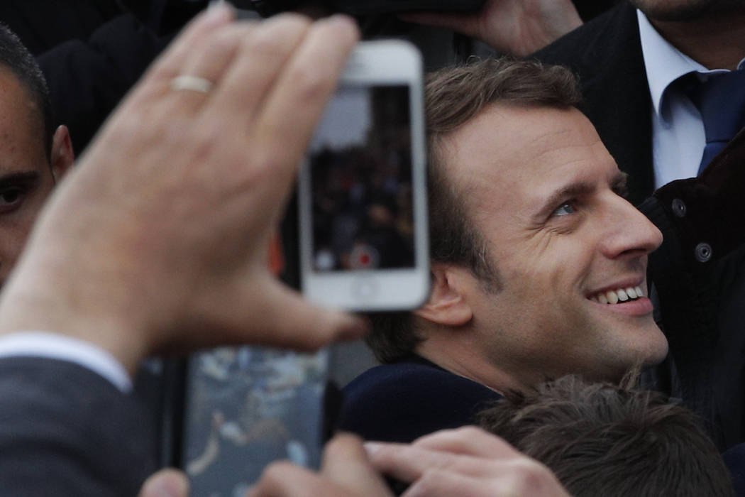 French independent centrist presidential candidate Emmanuel Macron shakes hands with well-wishers as he leaves the polling station after casting his ballot in the presidential runoff election in L ...