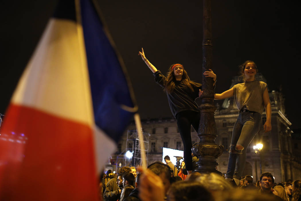 Women dance on a street lamp at the Louvre museum where Emmanuel Macron celebrated his victory, Sunday, May 7, 2017 in Paris. Speaking to thousands of supporters from the Louvre Museum's courtyard ...