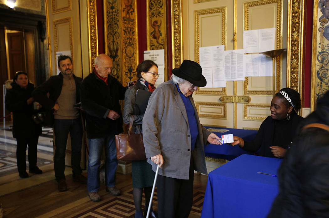 People line up to vote in the French presidential election at a polling station in Paris, France Sunday, May 7, 2017. Voters across France are choosing a new president in an unusually tense and im ...