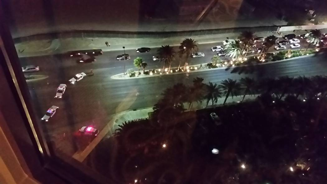 Police cars congregate outside the Hilton Grand Vacations time share on the Strip on Saturday night after an exchange of gunfire in the valet area. One man died, one was injured. (Dan Henry/Specia ...
