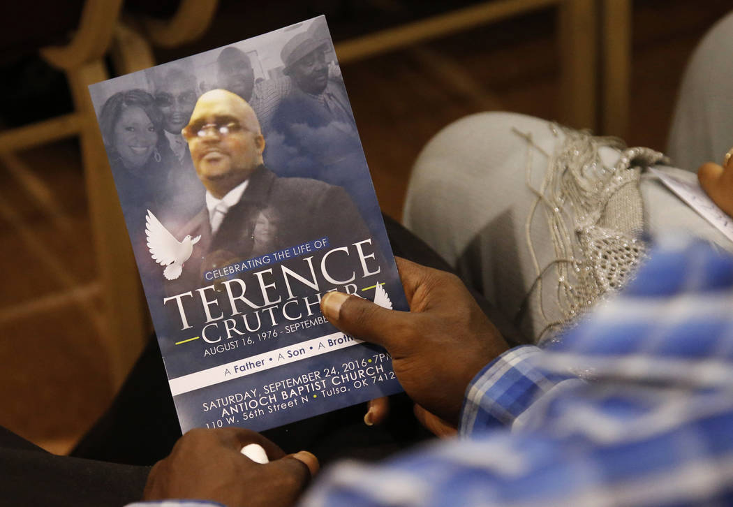 A man holds a copy of the program for the funeral of Terence Crutcher during services to honor him in Tulsa, Okla., Sept. 24, 2016. Crutcher was fatally shot Sept. 16 by Tulsa police officer Betty ...