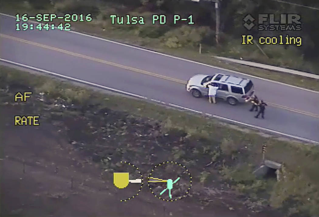In an image made from video, Terence Crutcher, left, with his arms held up, is pursued by police officers as he walks next to his stalled SUV moments before he was shot and killed by one of the of ...