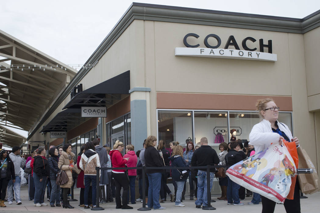 FILE - In this Friday, Nov. 27, 2015, file photo, shoppers wait in line outside a Coach factory outlet store at the Cincinnati Premium Outlets, in Monroe, Ohio. Coach is buying rival luxury handba ...