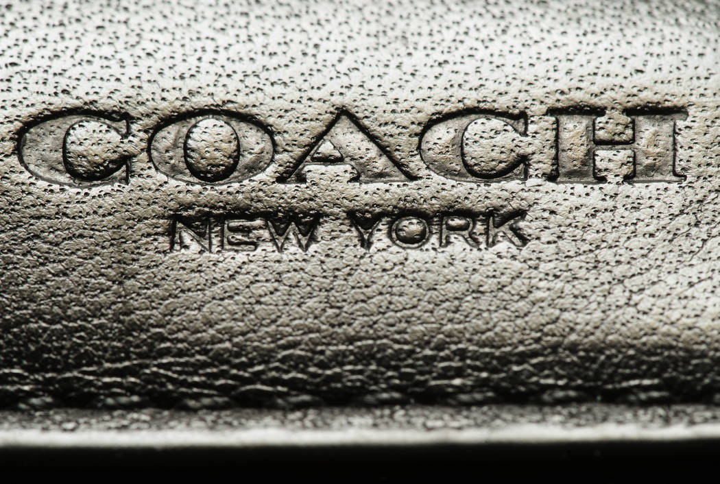 This photo shows a Coach brand logo on a leather wallet in Philadelphia, Monday, May 8, 2017. Coach will spend $2.4 billion for Kate Spade, tying together two premier brands in the luxury goods se ...