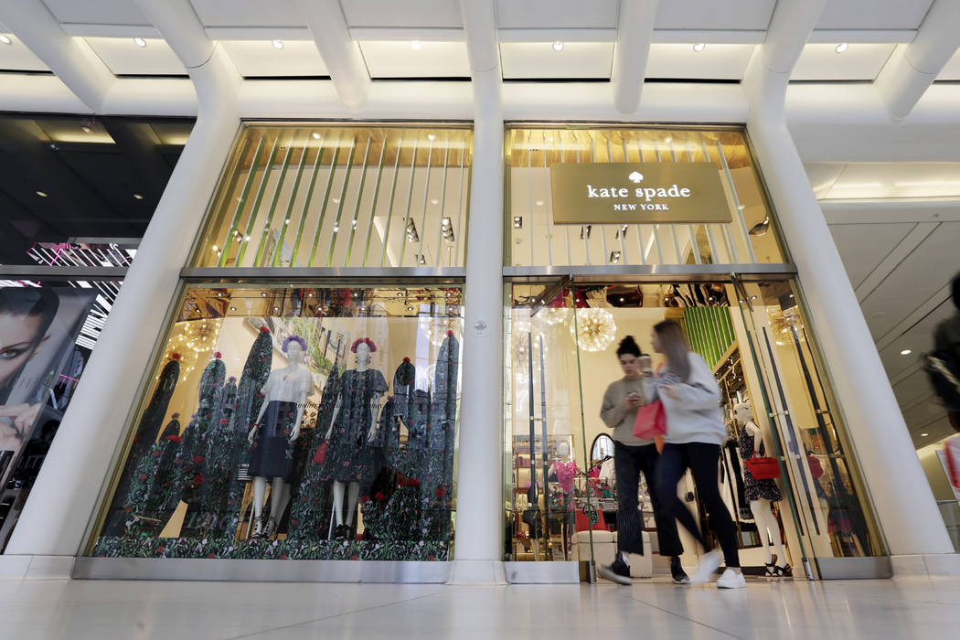 Shoppers leave a Kate Spade store in New York, Monday, May 8, 2017. Coach will spend $2.4 billion for Kate Spade, tying together two premier brands in the luxury goods sector that have fought to s ...
