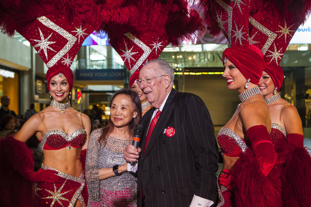 Lily Chu of Las Vegas, left, takes a photo with former Las Vegas Mayor Oscar Goodman and Viva Las Vegas showgirls during a celebration of tourism hosted by the Las Vegas Convention and Visitors Au ...