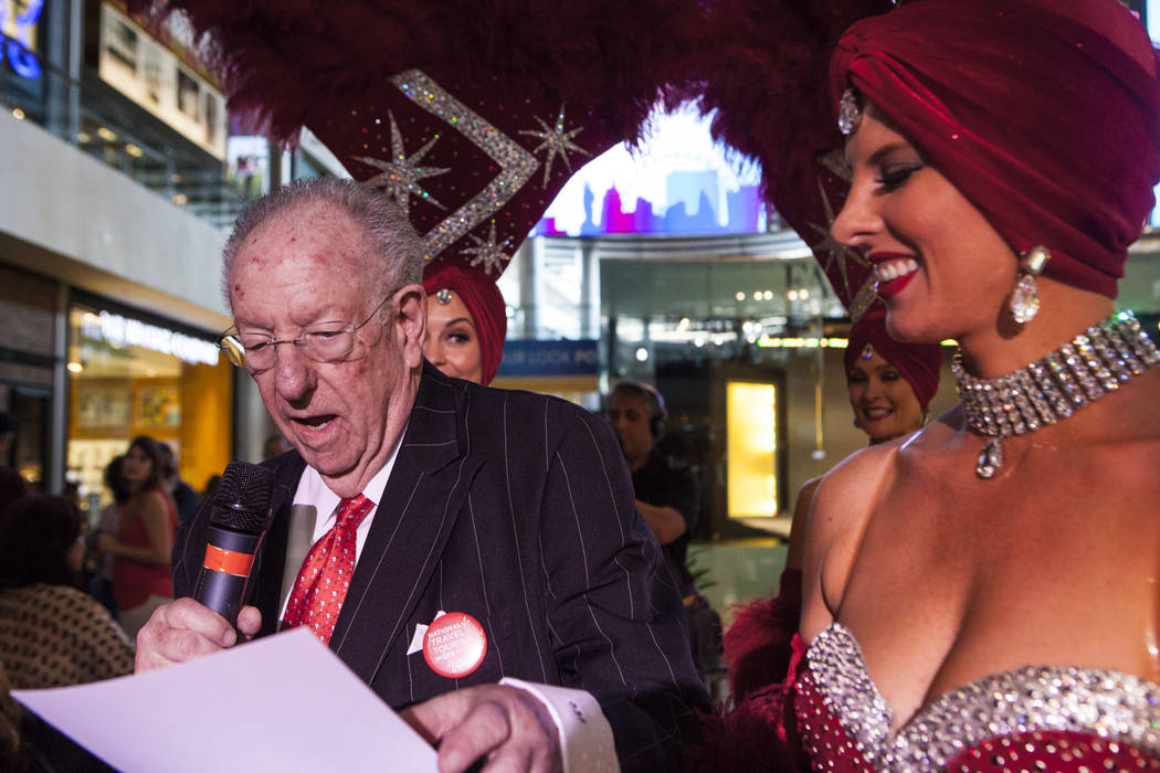 Former Las Vegas Mayor Oscar Goodman hands out prizes to the crowd with the help of a few Viva Las Vegas Showgirls during a celebration of tourism hosted by the Las Vegas Convention and Visitors A ...