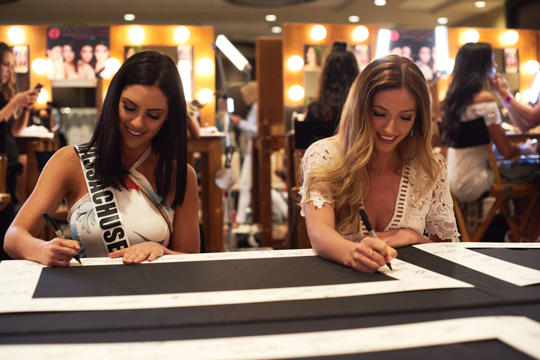 2017 Miss Massachusetts Julia Scaparotti and 2017 Miss Wyoming Mikaela Shaw sign souvenir items after arriving in Las Vegas on Thursday, May 4, 2017. (Miss Universe Organization)