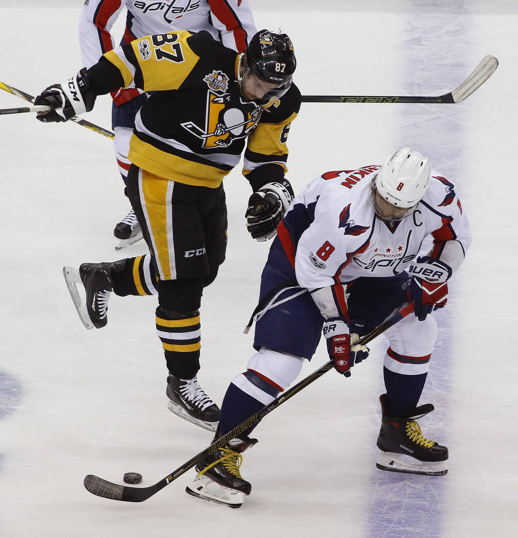 Washington Capitals' Alex Ovechkin (8) backhands a pass with Pittsburgh Penguins' Sidney Crosby (87) behind him during the period of Game 6 in an NHL Stanley Cup Eastern Conference semifinal hocke ...