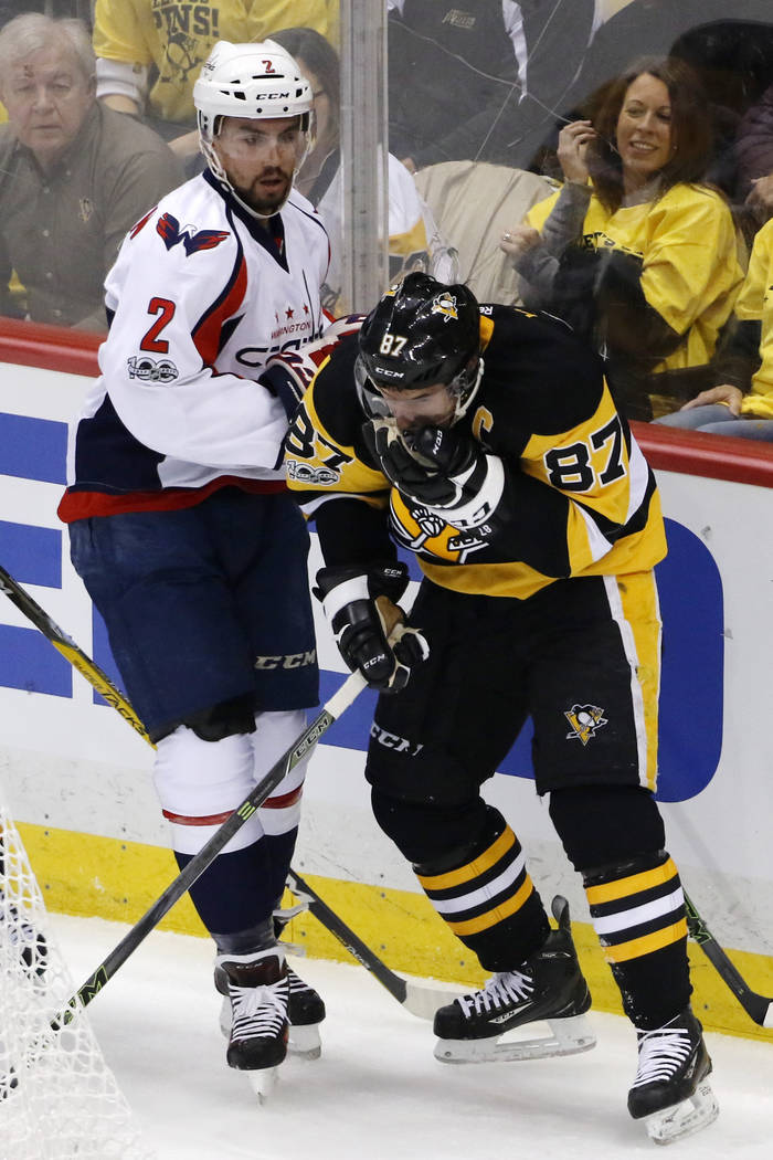 Pittsburgh Penguins' Sidney Crosby (87) holds his face after colliding with Washington Capitals' Matt Niskanen (2) during the first period of Game 6 in an NHL Stanley Cup Eastern Conference semifi ...