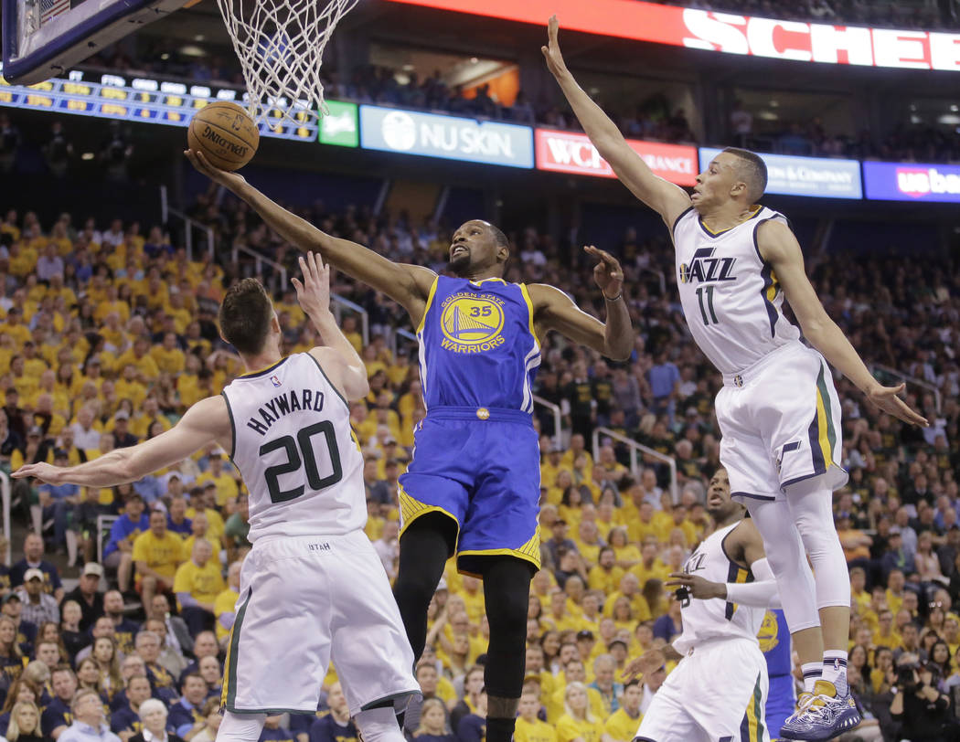 Golden State Warriors forward Kevin Durant (35) lays the ball up as Utah Jazz's Gordon Hayward (20) and Dante Exum (11) defend in the first half during Game 4 of the NBA basketball second-round pl ...