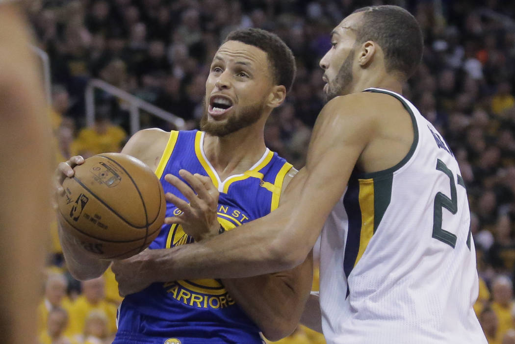 Golden State Warriors guard Stephen Curry, left, goes to the basket as Utah Jazz center Rudy Gobert (27) defends in the first half during Game 4 of the NBA basketball second-round playoff series M ...