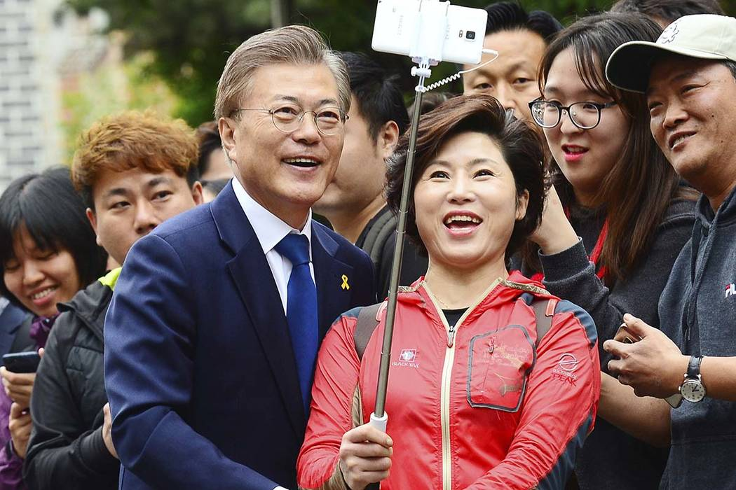 South Korean presidential candidate Moon Jae-in, front left, of the Democratic Party takes pictures with a supporter after voting for a presidential election at a junior high school in Seoul, Sout ...