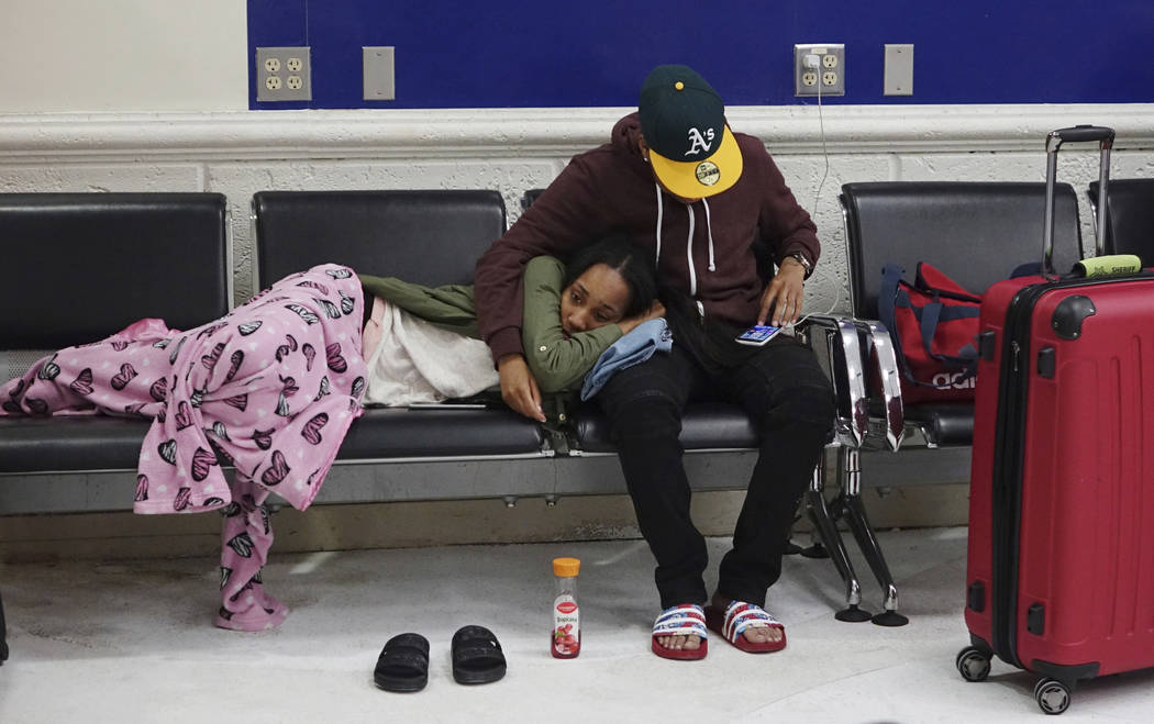 Latreece Smith rests as her friend Tamari Cameron checks flight information, Tuesday, May 9, 2017, at the Fort Lauderdale-Hollywood International Airport in Fort Lauderdale, Fla. Skirmishes involv ...