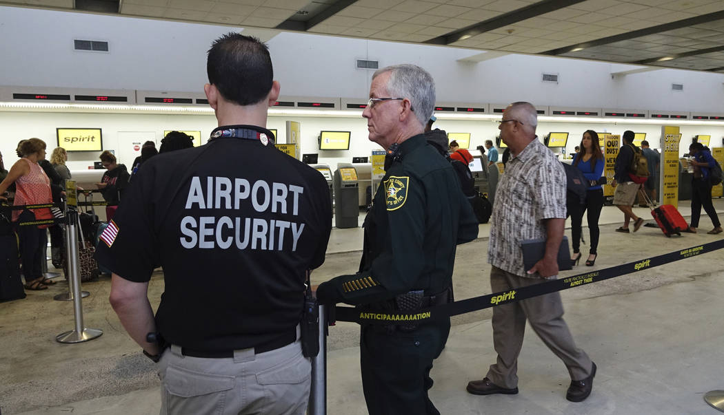 Airport Security and a Broward Sherriff's Deputy keep an eye on the line at Spirit Airlines, Tuesday, May 9, 2017, at the Fort Lauderdale-Hollywood International Airport in Fort Lauderdale, Fla. S ...