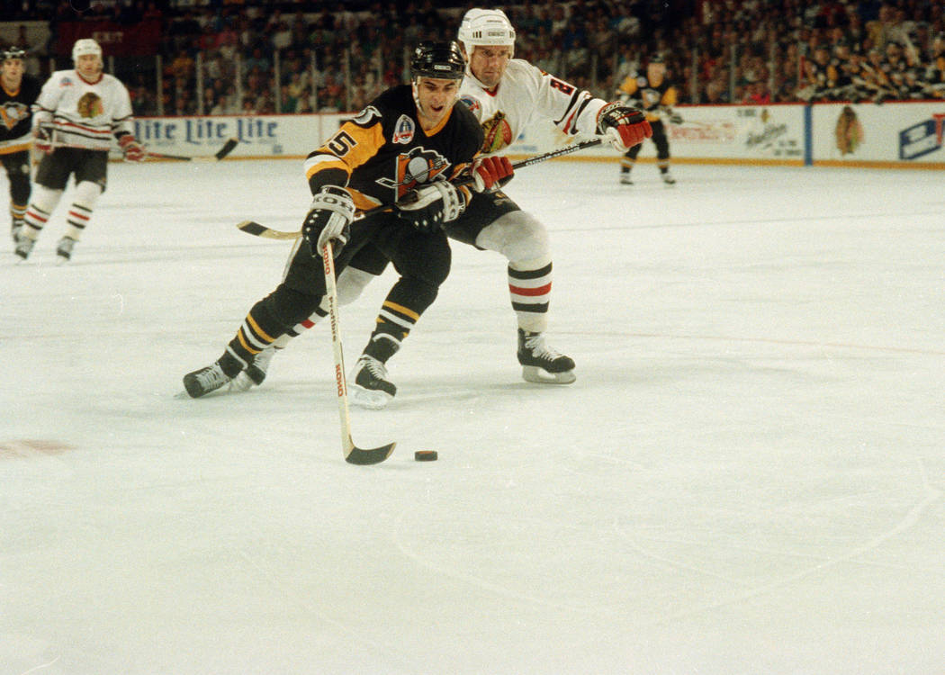 The Pittsburgh Penguins' Kevin Stevens, left, slips past the Chicago Blackhawks' Rod Buskas on his way to the Penguins' first goal during the first period of Game 4 in the Stanley Cup finals Monda ...