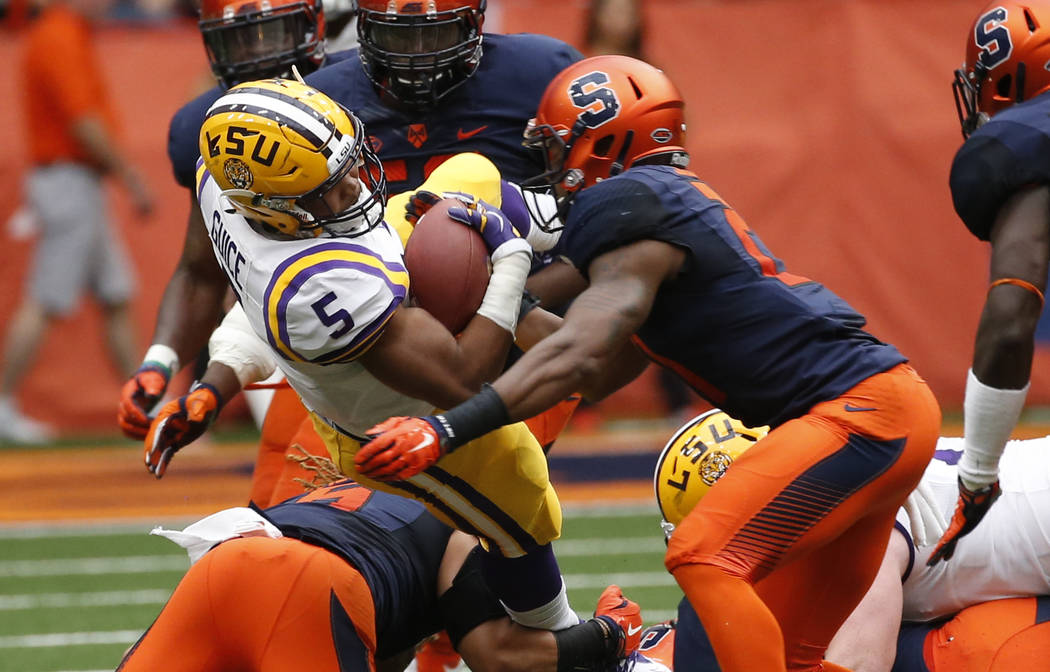 LSU running back Derrius Guice (5) is hit by Syracuse safety Chauncey Scissum (21) during the first half of an NCAA college football game on Saturday, Sept. 26, 2015, in Syracuse, N.Y. (AP Photo/M ...