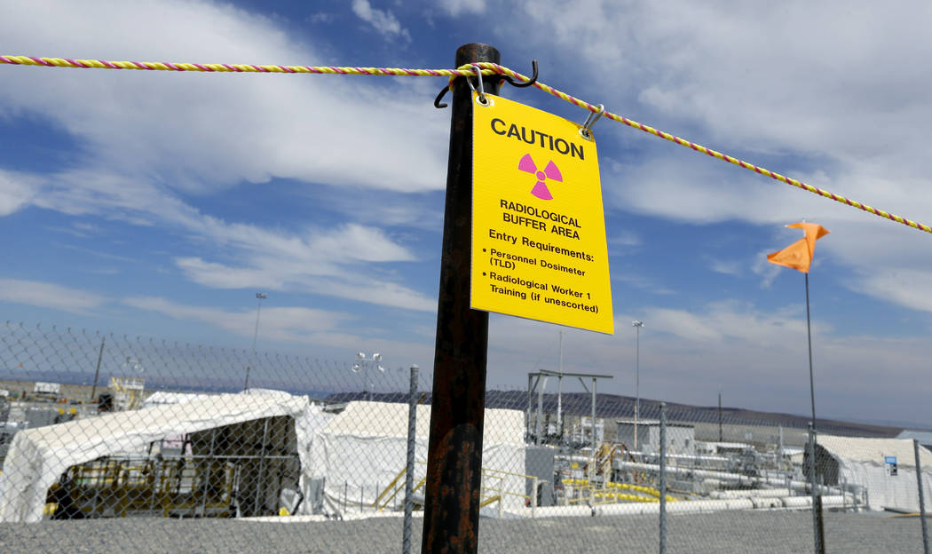 "sign warns of radioactivity near a wind direction flag indicator at the ""C"" tank farm on the Hanford Nuclear Reservation near Richland, Wash. on  July 9, 2014. (Ted S. Warren/AP)"