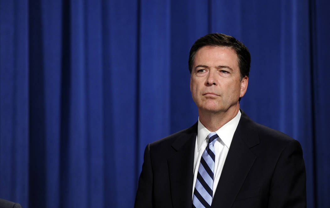 FBI Director James Comey listens during a news conference announcing a deal between the U.S. government and French bank BNP Paribas at the Justice Department in Washington, Monday, June 30, 2014.  ...