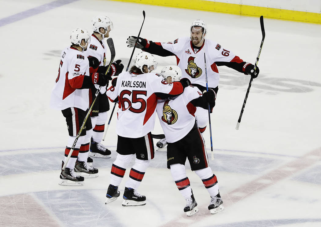 Ottawa Senators' Mark Stone (61) and Erik Karlsson (65) celebrate with teammates during the third period of Game 6 of an NHL hockey Stanley Cup second-round playoff series, Tuesday, May 9, 2017, i ...