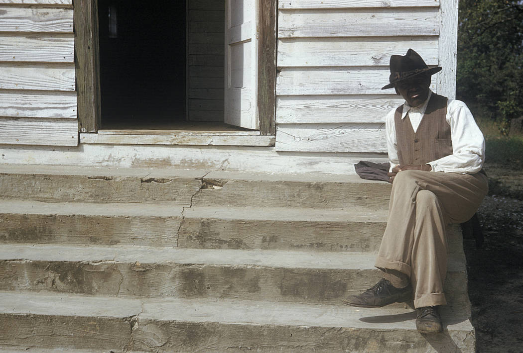 In this 1950's photo released by the National Archives, a man included in a syphilis study sits on steps in front of of a house in Tuskegee, Alabama. National Archives via AP