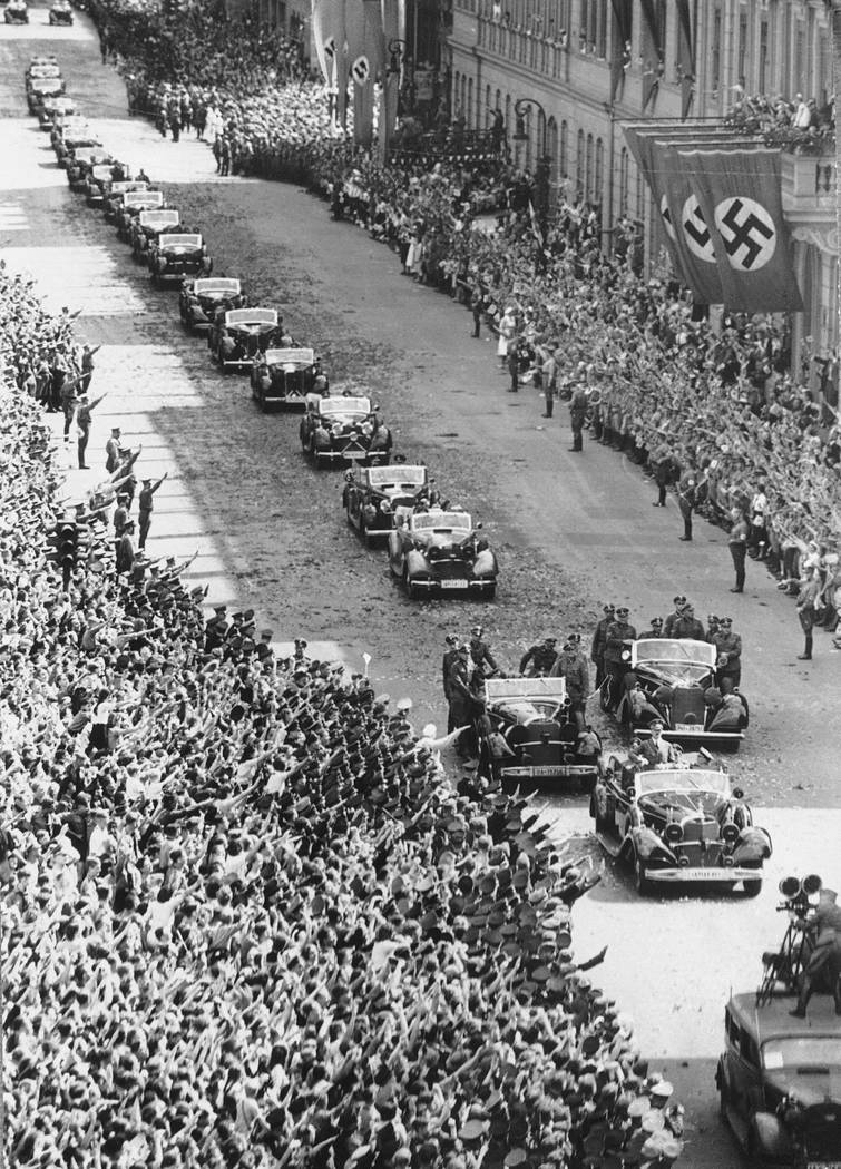 German Chancellor Adolf Hitler stands in the front car of a motorcade upon his arrival at the chancellery in Berlin on July 6, 1940, after returning from Compiegne, where France surrendered to Ger ...