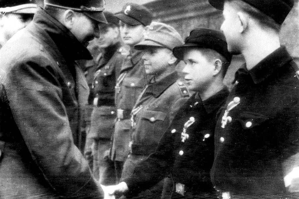 Adolf Hitler shakes hands with 12-year-old Alfred Czech, a Hitler Youth soldier, after the young veteran of battles in Pomerania and Upper and Lower Silesia was awarded the Iron Cross at Hitler's  ...