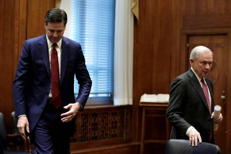 U.S. Attorney General Jeff Sessions, right, and FBI Director James Comey take seats before a meeting with heads of federal law enforcement components at the Justice Department in Washington, Feb.  ...