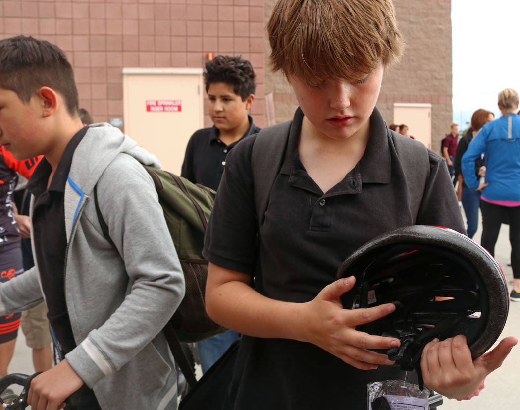 Matthew Nichols, 12, center, is given a helmet for the Bike to School event at Ralph Cadwallader Middle School, Wednesday, May 10, 2017. Gabriella Benavidez Las Vegas Review-Journal @latina_ish