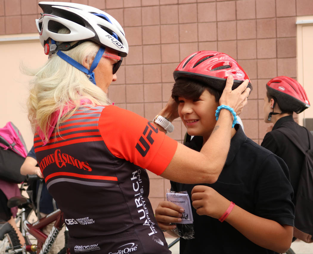 Breakaway Cycling member Kristi Peressini, left, gives Camron Sanchez, 11, a helmet during the Bike to School event at Ralph Cadwallader Middle School, Wednesday, May 10, 2017. Gabriella Benavidez ...