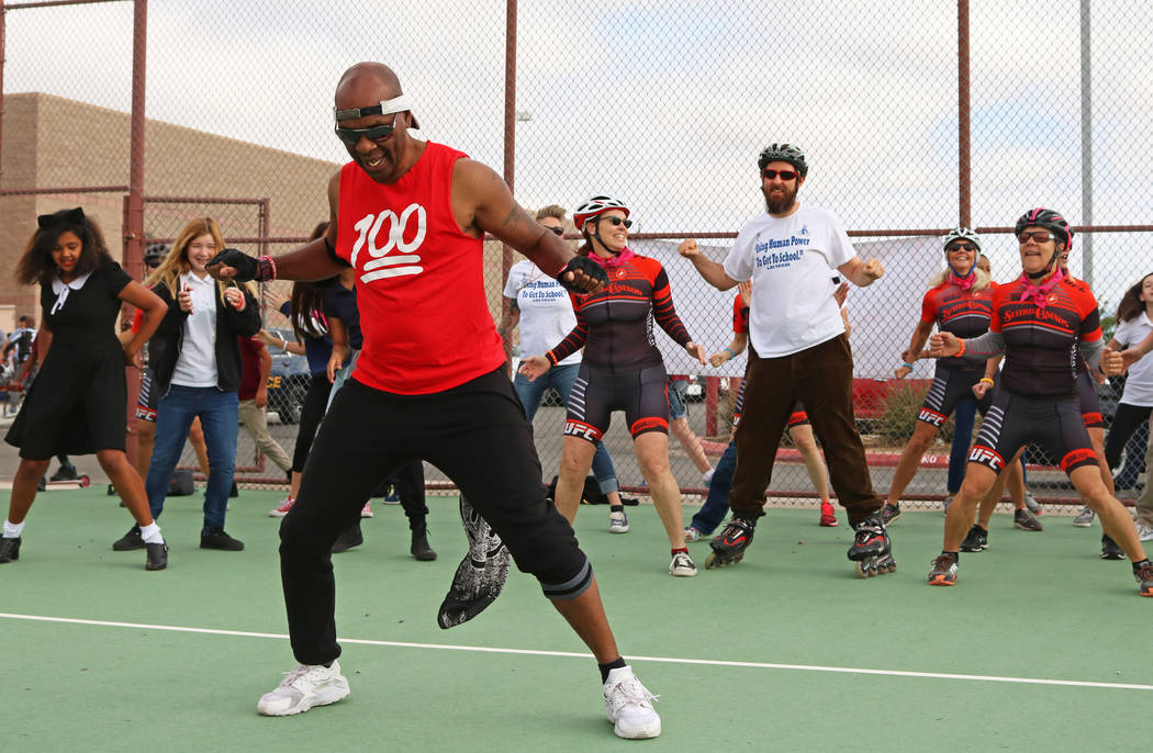 Jerry Johnson, left, leads Ralph Cadwallader Middle School students and faculty, and Breakaway Cycling members, in a dance routine during the Bike to School event, Wednesday, May 10, 2017. Gabriel ...