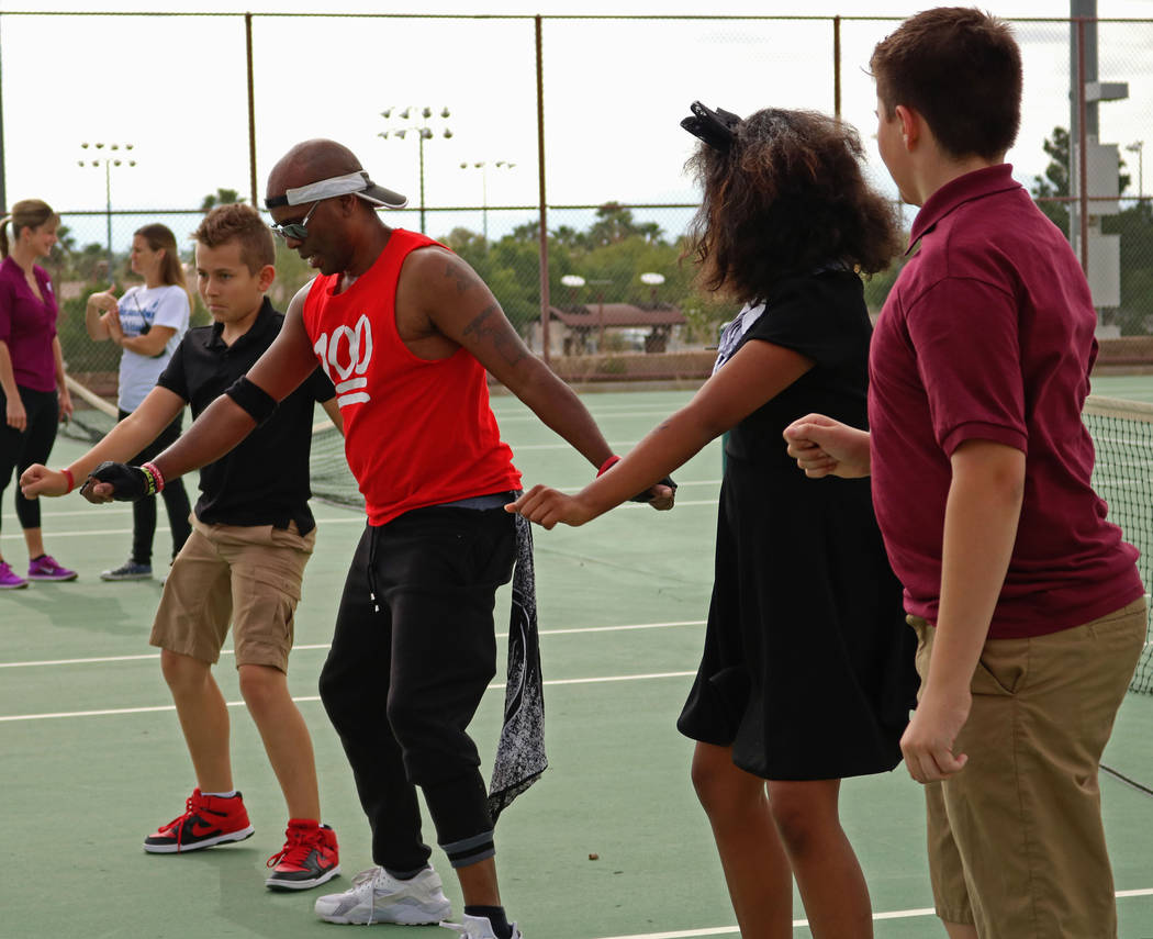 Jerry Johnson, second left, and Cadwallader Middle School students lead a fitness routine during the Bike to School event, Wednesday, May 10, 2017. Gabriella Benavidez Las Vegas Review-Journal @la ...
