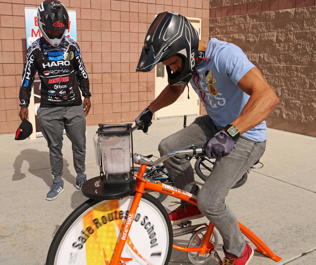 Professional BMX riders Eric Sweets, left, and Ricardo Laguna, test a stationary bike that powers a blender during the Bike to School event at Ralph Cadwallader Middle School, Wednesday, May 10, 2 ...