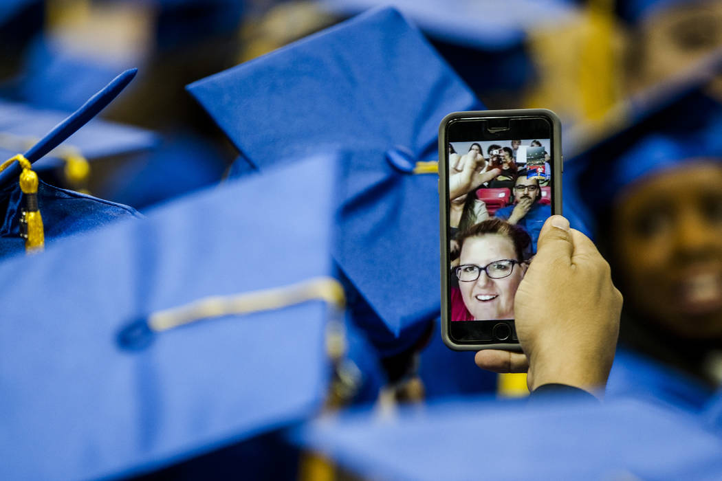 A College of Southern Nevada graduate talks with people on FaceTime before the start of commencement at the Thomas and Mack Center in Las Vegas on Monday, May 15, 2017. Patrick Connolly Las Vegas  ...