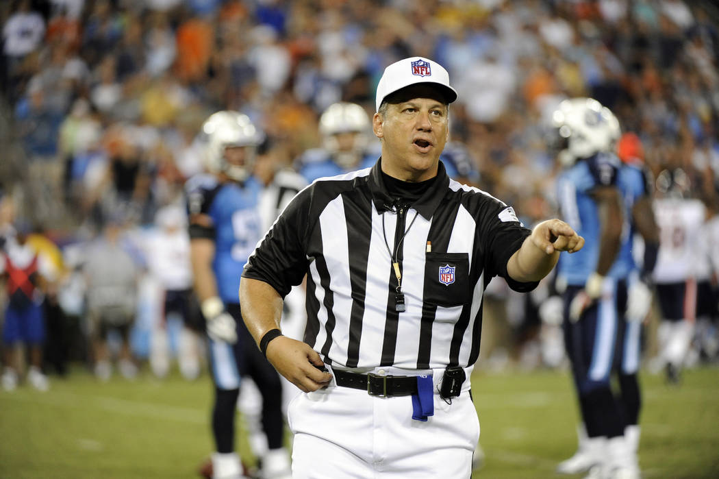 In this Aug. 27, 2011, file photo, referee Alberto Riveron makes a call in the second quarter of an NFL football preseason game between the Chicago Bears and the Tennessee Titans in Nashville, Ten ...