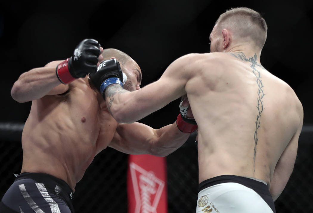 Conor McGregor, right, fights Eddie Alvarez during a lightweight title mixed martial arts bout at UFC 205, early Sunday, Nov. 13, 2016, at Madison Square Garden in New York. (AP Photo/Julio Cortez)
