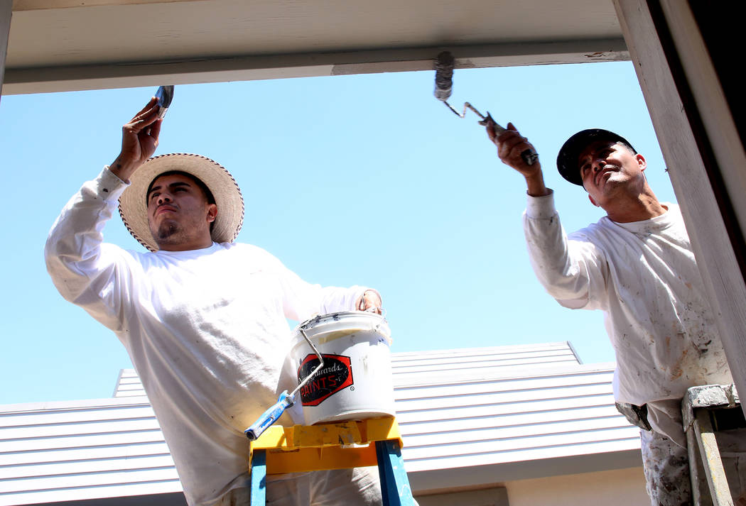 Nock Martinez, left, and Orlando Saavedra paint a house on Thursday, May 11, 2017, in Las Vegas. Keller Williams Realty agents and partner businesses renovate eight aging housing units for homeles ...