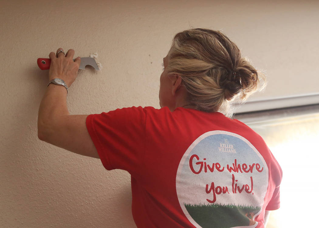 Volunteer Joan Kilton patches a hole in the wall on Thursday, May 11, 2017, in Las Vegas. Keller Williams Realty agents and partner businesses renovate eight aging housing units for homeless youth ...