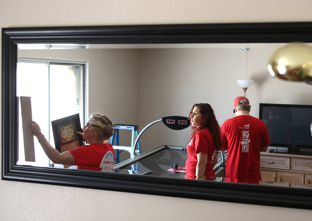 Volunteers Joan Kilton, left, and Allison Wax, center, install wall decorations on Thursday, May 11, 2017, in Las Vegas. Keller Williams Realty agents and partner businesses renovate eight aging h ...