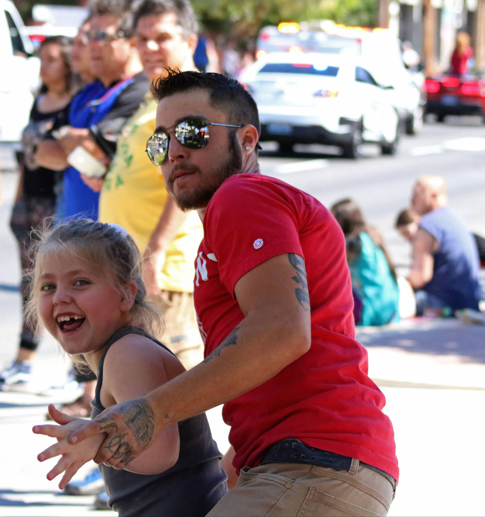 Alicia Brown, 8, dances with her father as the Mojave High School marching band performs during the Helldorado Days Parade in downtown Las Vegas, Saturday, May 13, 2017. Gabriella Benavidez Las Ve ...