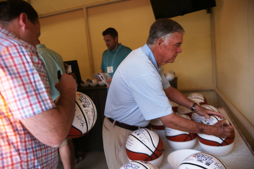 Jack Murphy, coach for Northern Arizona University, left, and Coach Mike Montgomery sign a basketball at the Coach vs. Cancer fundraiser event on Sunday, May 21, 2017, at the MGM Grand hotel-casin ...