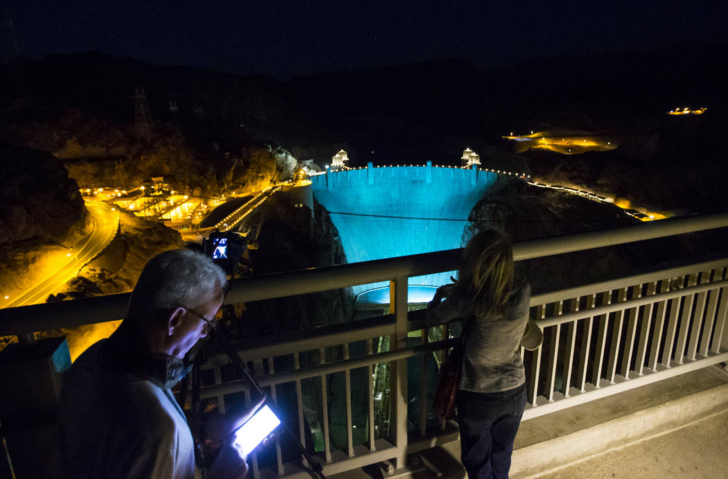 Henderson resident Greg Hergesell, left, with wife Patricia, checks his phone for the time of the moon rise while photographing the Hoover Dam, lit up turquoise to promote lung cancer awareness, f ...