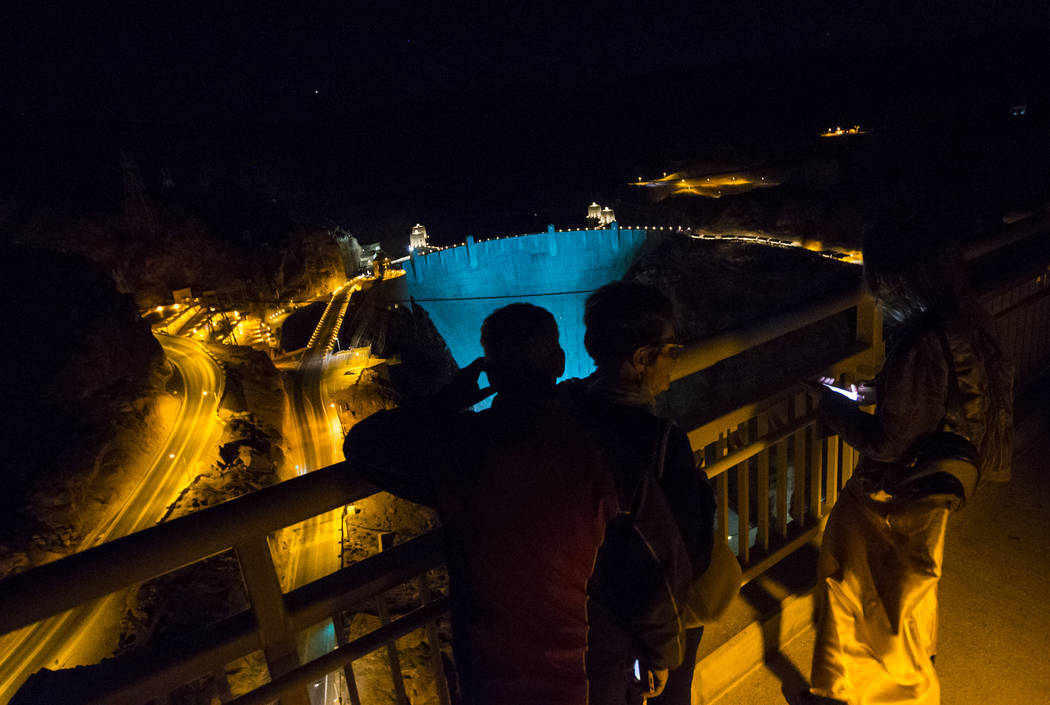 People take in the sights of the Hoover Dam, lit up turquoise to promote lung cancer awareness, from O'Callaghan-Tillman Memorial Bridge on Thursday, May 11, 2017. Chase Stevens Las Vegas Review-J ...