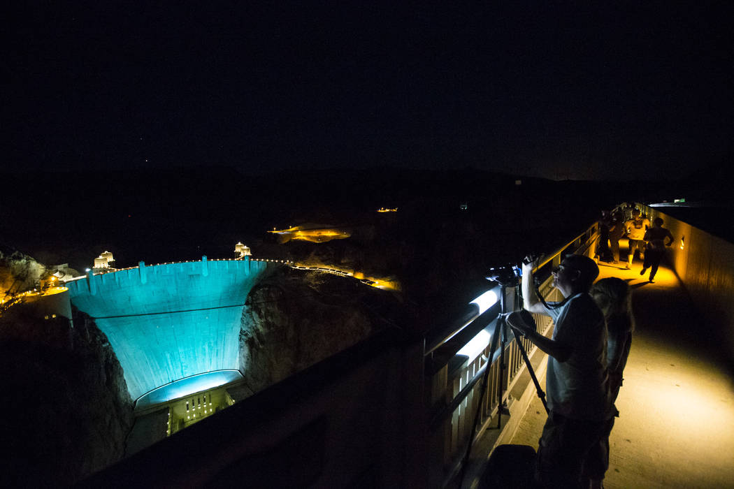 Henderson resident Greg Hergesell, right, photographs the Hoover Dam, lit up turquoise to promote lung cancer awareness, from O'Callaghan-Tillman Memorial Bridge on Thursday, May 11, 2017. Chase S ...