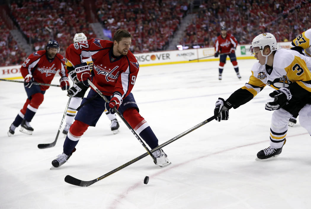 Washington Capitals center Evgeny Kuznetsov (92), from Russia, who lost his helemt, passes the puck past Pittsburgh Penguins defenseman Olli Maatta (3), from Finland, during the second period of G ...