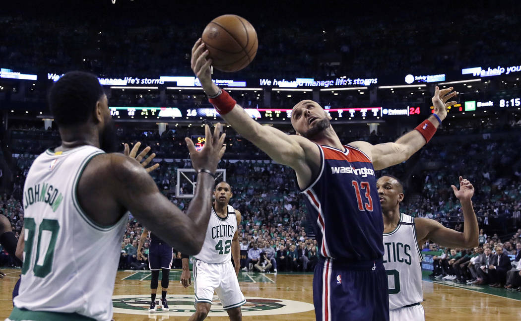Washington Wizards center Marcin Gortat (13) grabs a rebound between Boston Celtics forward Amir Johnson (90) and guard Avery Bradley, right, during the first quarter of Game 5 of a second-round N ...