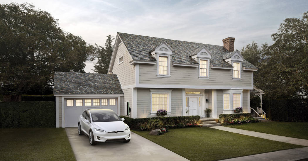 This photo provided by Tesla shows a house with Tesla's new slate solar roof tiles. As of Wednesday, May 10, 2017, customers worldwide could order a solar roof on Tesla's website. The glass tiles  ...