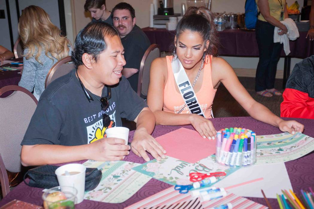 Miss Florida Linette De Los Santos works with a new friend with Best Buddies International at Mandalay Bay on Sunday, May 7, 2017, in Las Vegas. (Miss Universe Organization)