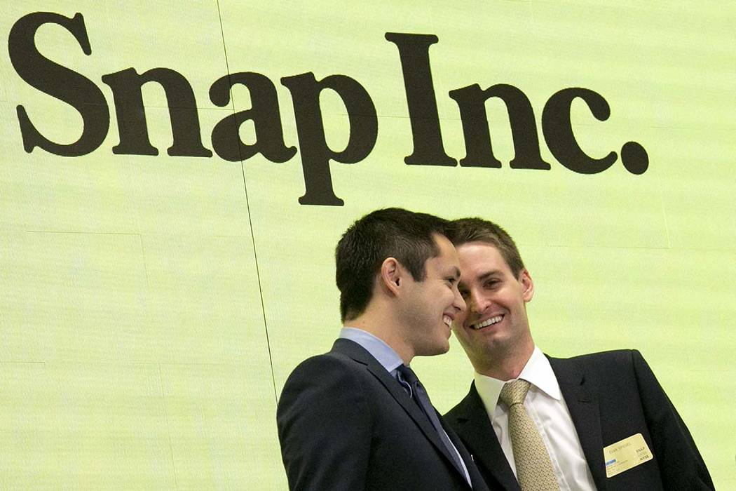 In this Thursday, March 2, 2017, file photo, Snapchat co-founders Bobby Murphy, left, and CEO Evan Spiegel ring the opening bell at the New York Stock Exchange as the company celebrates its IPO. R ...